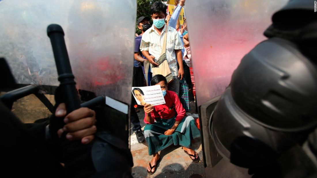 A protester holds a Suu Kyi poster as he sits in front of police in Yangon on February 19.