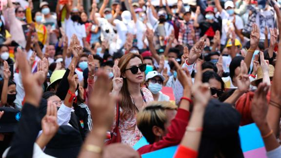Protesters flash the three-fingered salute during a rally in downtown Yangon on February 19.