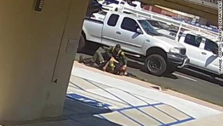 Video from a nearby surveillance camera shows two Orange County sheriff's deputies struggling with 42-year-old Kurt Reinhold, who they initially stopped for jaywalking.