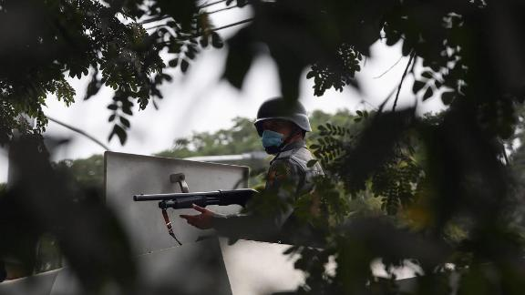 A police officer aims a gun toward protesters during a demonstration in Mandalay on February 20.