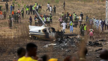 People and rescuers gather at the site where a Nigerian air force plane crashed while approaching the Abuja airport runway on Sunday