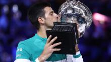 MELBOURNE, AUSTRALIA - FEBRUARY 21: Novak Djokovic of Serbia holds the Norman Brookes Challenge Cup as he celebrates victory in his Men's Singles Final match against Daniil Medvedev of Russia  during day 14 of the 2021 Australian Open at Melbourne Park on February 21, 2021 in Melbourne, Australia. (Photo by Cameron Spencer/Getty Images)