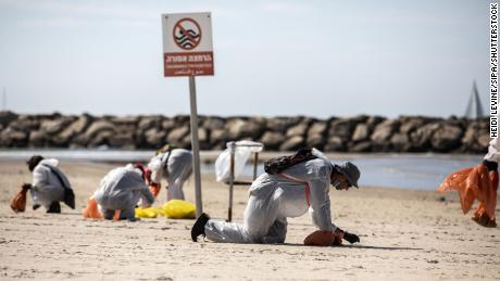 Volunteers wearing protective clothing search for tar along Israel's coast in Herzilya Pituah, north of Tel Aviv on February 21.