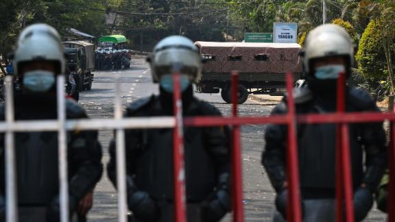 Police stand guard near the US Embassy in Yangon as protesters take part in an anti-coup demonstration on February 22.