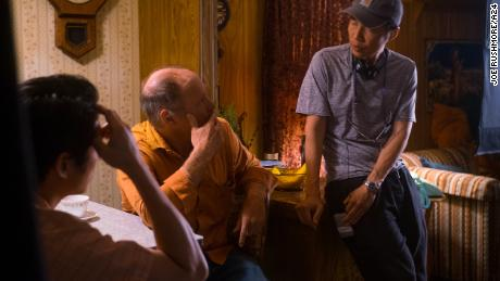 "Writer-director Lee Isaac Chung (right) with actors Steven Yeun (left) and Will Patton (center) on the set of ""Minari."""