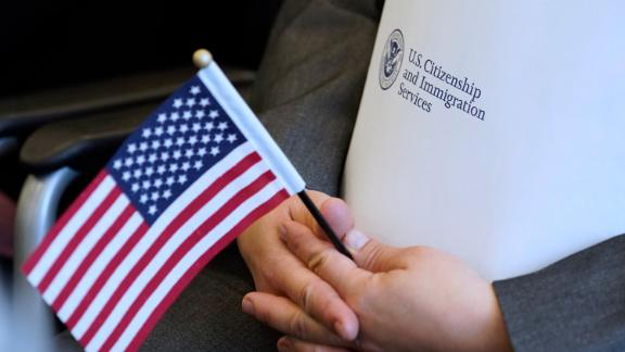 In this April 10, 2019, file photo, an applicant holds an American flag and a packet while waiting to take the oath to become a US citizen at a naturalization ceremony in Salt Lake City.