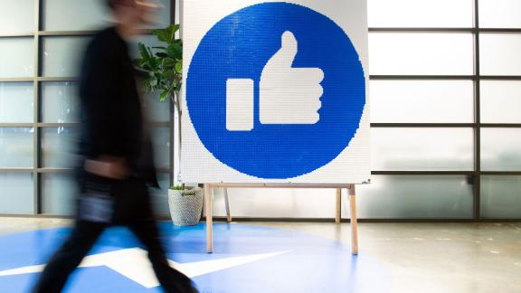 "A Facebook employee walks by a sign displaying the ""like"" sign at Facebook"