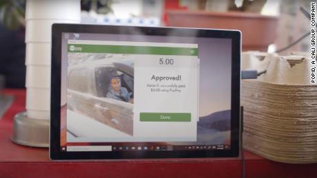 A customer uses PopID's facial-recognition system to pay for food at a drive-thru.