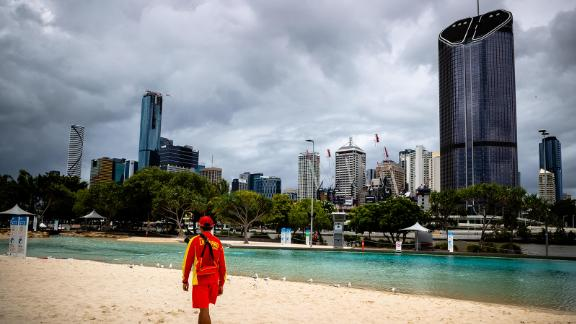 """A lifeguard stands watch over a deserted South Bank beach on the first day of a snap lockdown in Brisbane on January 9, 2021, with officials elsewhere in Australia on """"high alert"""" over the emergence of more contagious strains of the Covid-19 coronavirus. (Photo by Patrick HAMILTON / AFP) (Photo by PATRICK HAMILTON/AFP /AFP via Getty Images)"""
