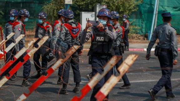 A police officer films protesters near the Indonesian Embassy in Yangon on February 24.