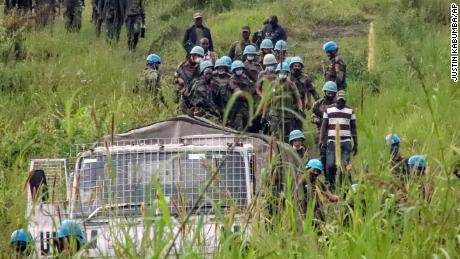 United Nations peacekeepers remove bodies from the area of the attack in North Kivu province on Monday