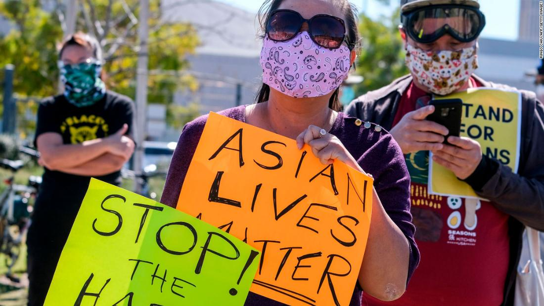 Demonstrators wearing face masks and holding signs take part in a rally to raise awareness of anti-Asian violence, near Chinatown in Los Angeles, California, on February 20, 2021. - The rally was organized in response to last month's fatal assault of Vicha Ratanapakdee, an 84-year-old immigrant from Thailand, in San Francisco. (Photo by RINGO CHIU / AFP) (Photo by RINGO CHIU/AFP via Getty Images)