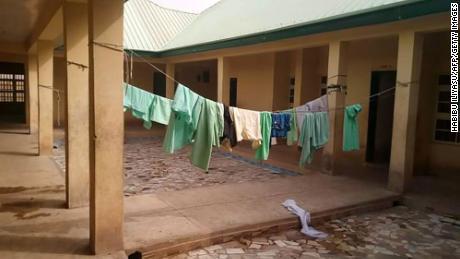 Os uniformes escolares ainda estão pendurados dentro do dormitório escolar abandonado após o ataque