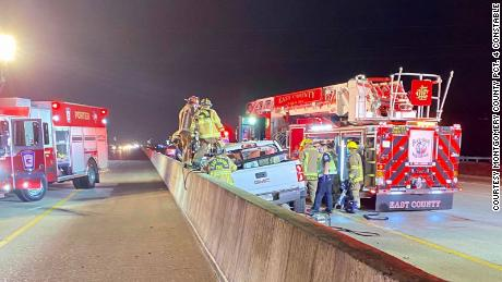 Firefighters examine a vehicle involved in a fatal accident on Interstate 59 in Texas on Thursday, February 25.