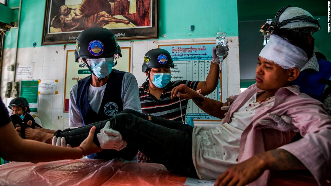 An injured protester receives medical attention in Mandalay after police and military forces cracked down on protests on February 26.