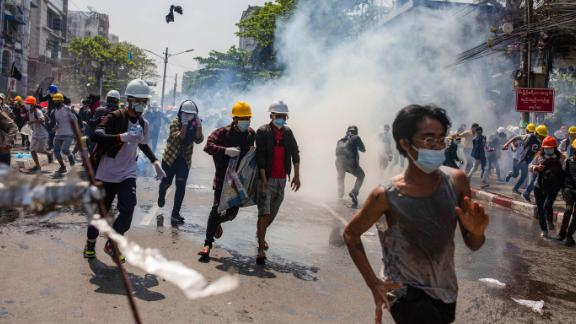 Protesters in Yangon run away from tear gas on March 1.