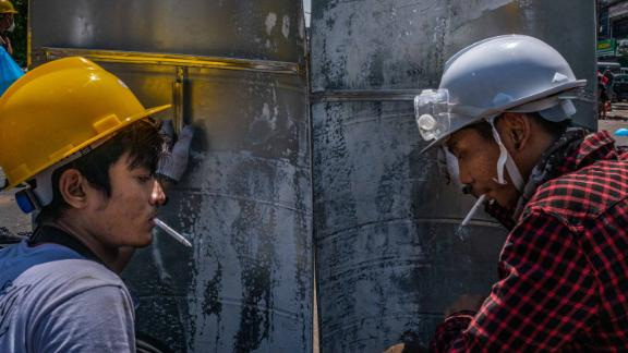 Protesters smoke behind shields during a demonstration in Yangon on March 1.