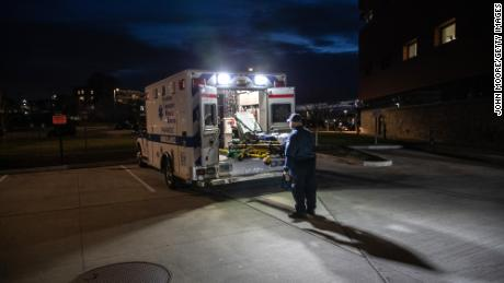 A paramedic loads a cleaned stretcher onto the back of an ambulance before heading out for another call. The pandemic has only exacerbated decades-long trends in American death rates described in a new report.