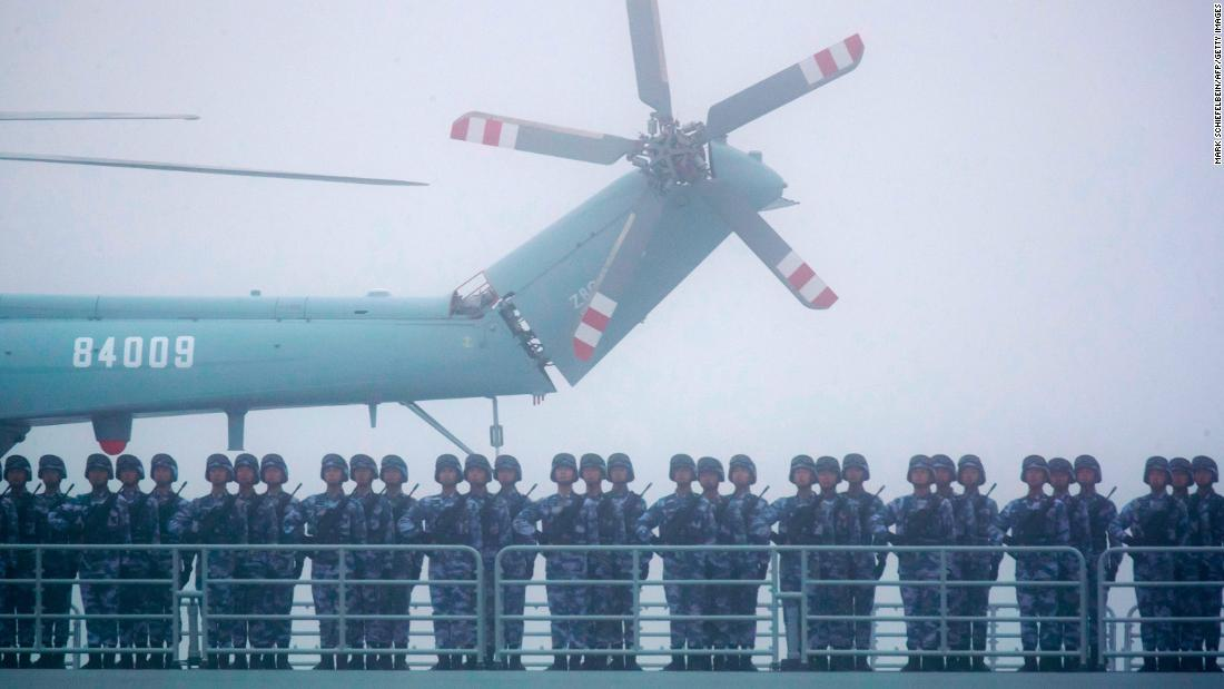 Soldiers stand on deck of the ambitious transport dock Yimen Shan of the PLA Navy as it participates in a parade in the sea near Qingdao, China, in 2019.
