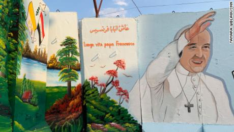 Blast walls which continue to surround the Our Lady of Salvation church are adorned with murals of Pope Francis in preparation for the historic papal visit.