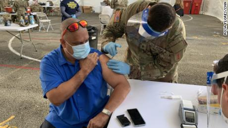 Guillermo Muñoz, a school principal in Miami-Dade County, receives a Johnson & Johnson vaccine shot Wednesday at a FEMA-run site at Miami Dade College.