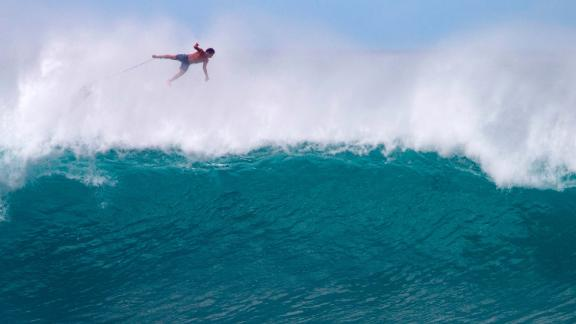 TOPSHOT - Hawaii's Billy Kemper falls off his board during the Da Hui Backdoor shootout at the Pipeline on Oahu's North Shore on January 13, 2019. (Photo by brian bielmann / AFP) / RESTRICTED TO EDITORIAL USE        (Photo credit should read BRIAN BIELMANN/AFP via Getty Images)