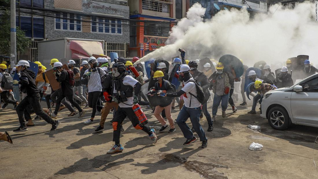 Anti-coup protesters run in Yangon on March 3. One of them discharged a fire extinguisher to counter the impact of tear gas fired by police.