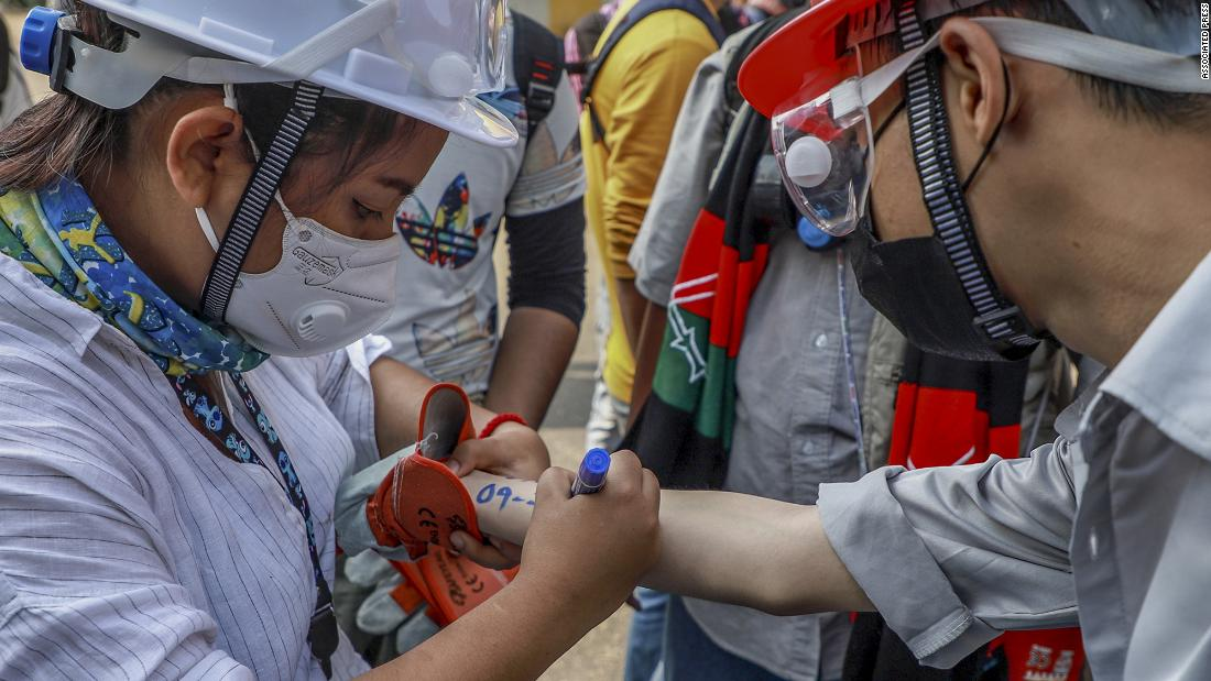 An anti-coup protester writes vital emergency information of another protester on his arm in Yangon.