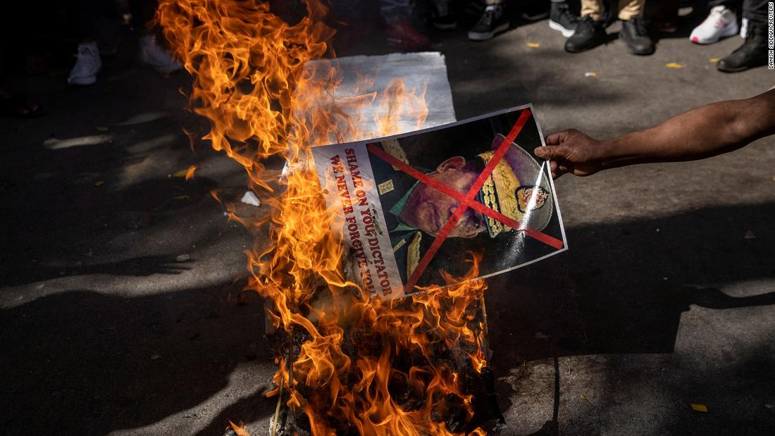 A citizen of Myanmar living in India burns a poster of Myanmar's military chief during a protest in New Delhi on March 3.