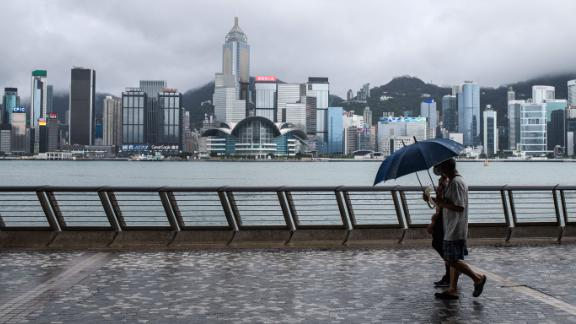 Two men use umbrellas on Kowloon's Tsim Sha Tsui waterfront that faces Victoria Harbour and the Hong Kong Island skyline (back), after Typhoon Higos swept past overnight in Hong Kong on August 19, 2020.
