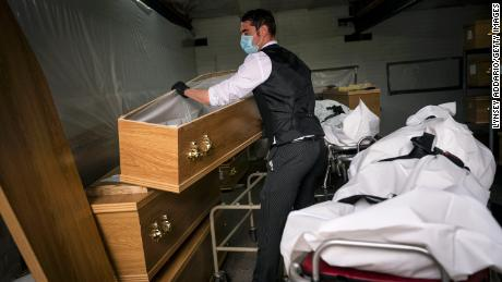 Jake Kill, a pallbearer and driver for Stoneman Funeral Services, selects coffins for Covid-19 victims at the funeral home in Surrey, England on May 22, 2020.