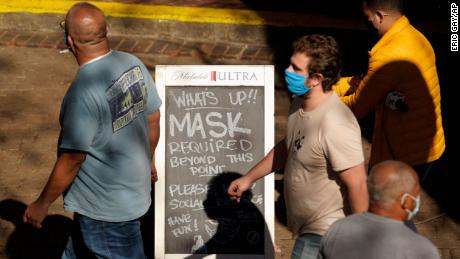 Visitors wearing face masks walk past a sign requiring masks at a restaurant along the River Walk, Wednesday, March 3, 2021, in San Antonio.