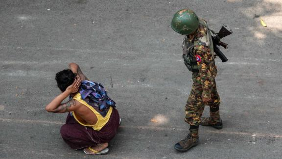 A soldier stands next to a detained man during a demonstration in Mandalay on March 3.