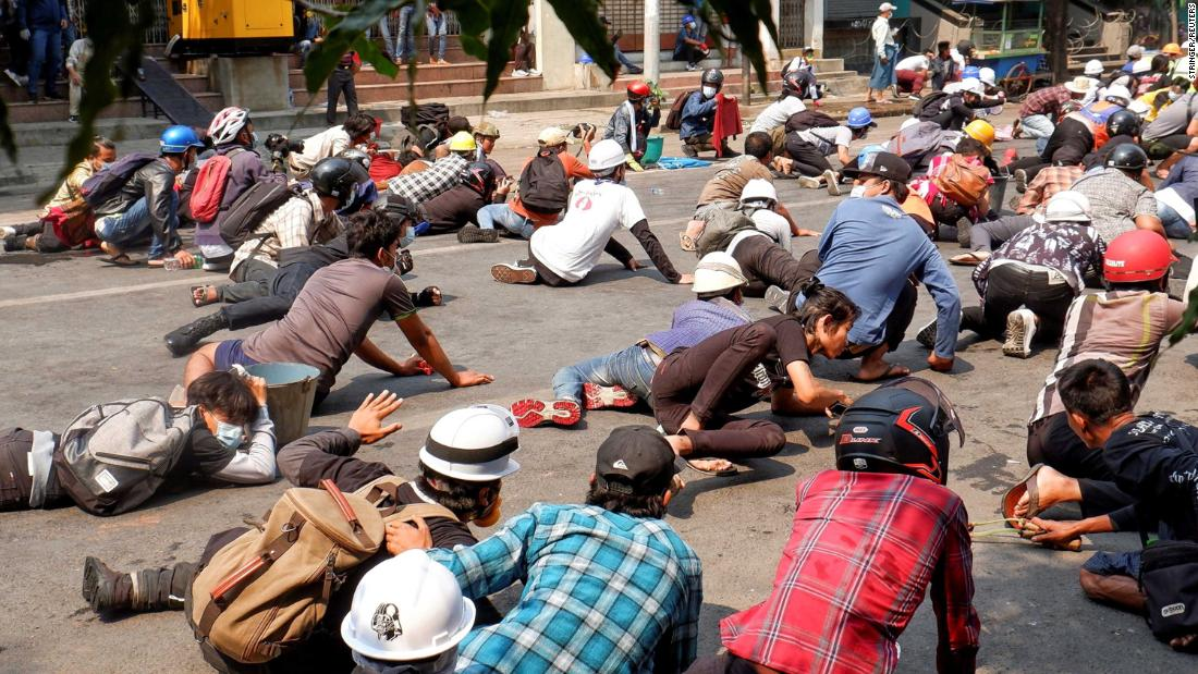 Protesters lie on the ground after police opened fire to disperse an anti-coup demonstration in Mandalay on March 3.