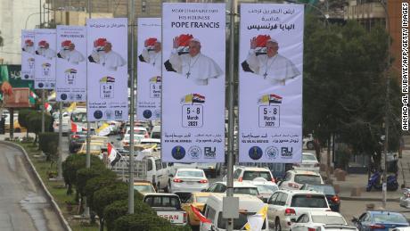 El tráfico pasa junto a carteles que dan la bienvenida al Papa a la capital iraquí en vísperas de su visita.
