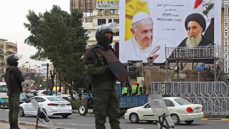 Los guardias de seguridad iraquíes se paran frente a una enorme valla publicitaria con retratos del Papa Francisco y el Gran Ayatolá Ali al-Sistani en el centro de Bagdad el 4 de marzo.