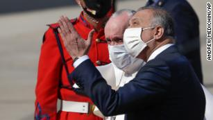 Pope Francis is greeted by Iraqi Prime Minister Mustafa al-Kadhimi as he arrives at Baghdad's international airport.