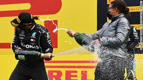 Lewis Hamilton and Stephanie Travers celebrate on the podium after the Styrian Grand Prix.