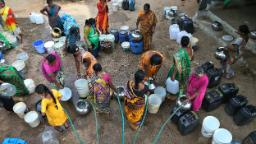 Indian women gather with utensils to collect water from a mobile water tanker at a slum area in Hyderabad, India, Wednesday, May 15, 2019. There is no direct supply of potable water at homes in most of the poor neighborhoods in the country. (AP Photo/Mahesh Kumar A.)