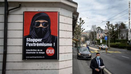 "A man wearing a face mask walks on February 4, 2021 in Lausanne past an electoral poster in favor of a ""burqa ban"" initiative reading in French: ""Stop extremism!"""