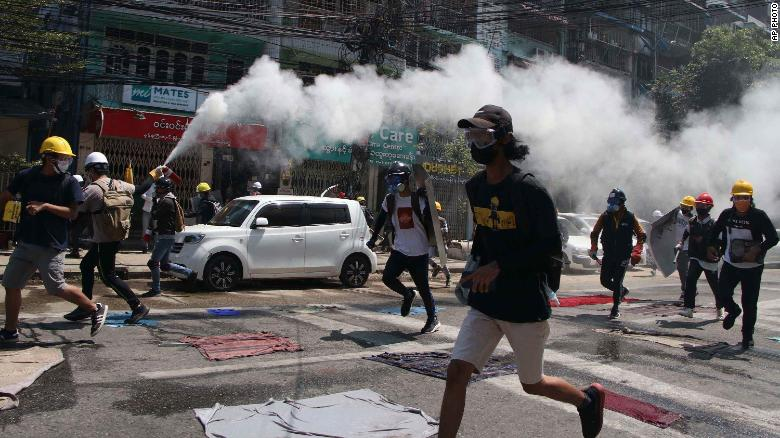 An anti-coup protester discharges a fire extinguisher to counter the impact of tear gas that was fired by police during a demonstration in Yangon, Myanmar, on Monday, March 8.