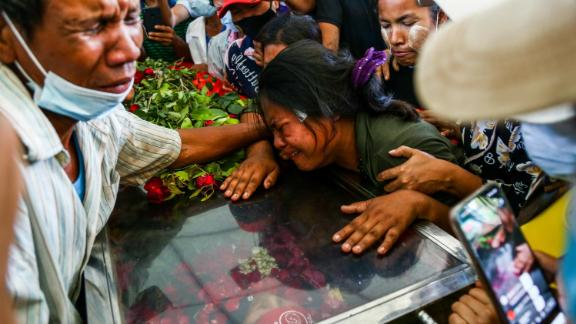 The wife of Phoe Chit, a protester who died during a demonstration, cries over her husband's coffin during his funeral in Yangon on March 5.