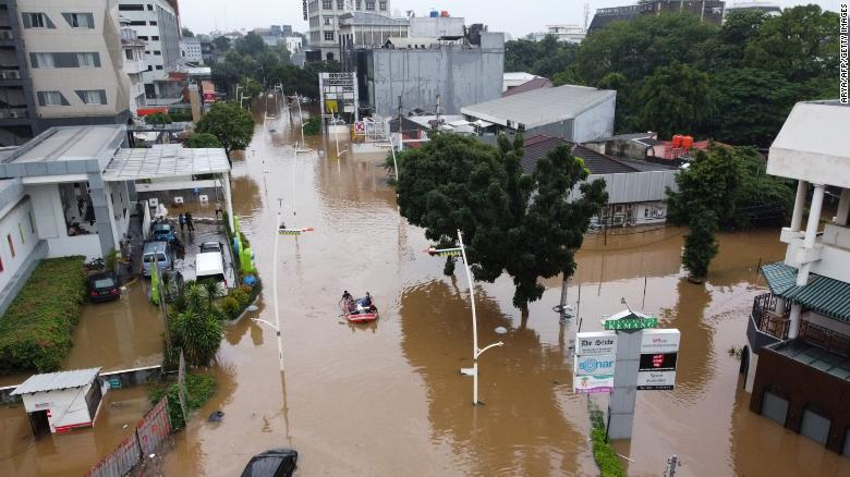 This aerial picture shows people rowing a raft over a flooded road in Jakarta on February 20, 2021, following heavy overnight rains. The combination of so many people and the multitude of rivers has made this city especially prone to relative sea level rise.