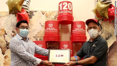 Marcos Perez (r) being honored for donating 120 gallons of blood.