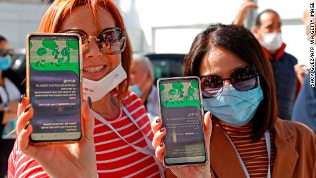 """People show off their """"green passes"""" in the Israeli coastal city of Tel Aviv on March 5, 2021."""
