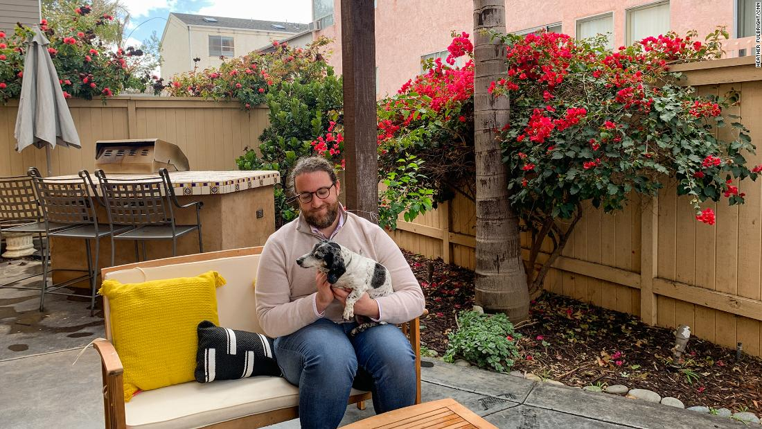 Ryan Mattison holds his roommate's dog in his new home in San Diego.