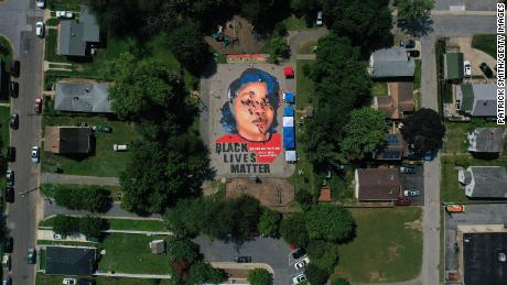 """In an aerial view from a drone, a large-scale ground mural depicting Breonna Taylor with the text """"Black Lives Matter"""" is seen being painted at Chambers Park on July 5, 2020 in Annapolis, Maryland."""
