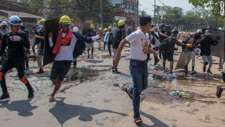 Anti-coup protesters retreat from the front lines after riot policemen fire sound-bombs and rubber bullets in Yangon, Myanmar, on March 11.