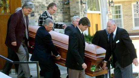 Carriers accompany the coffin of Canadian golf legend Norman.