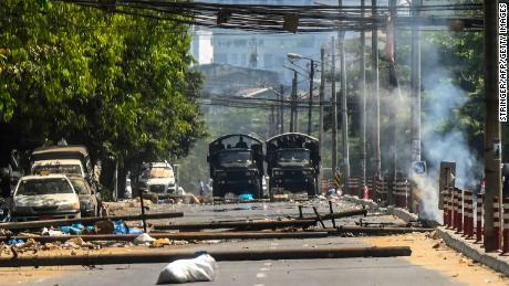 Military trucks are seen near a burning barricade, erected by protesters then set on fire by soldiers, during a crackdown on demonstrations against the military coup in Yangon on March 10.